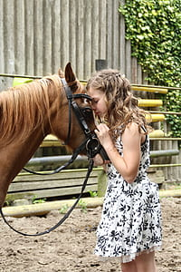 girls wearing floral dress beside the horse