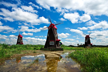 three brown-and-red windmills photo during daytime
