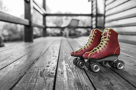 selective color photography of pair of red roller skates