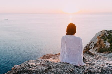 woman wearing white cover-ups sitting on rocky hill with the view of body of water during golden hour