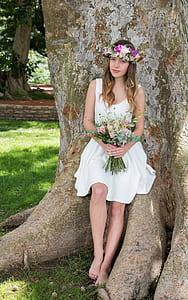 woman in white sleeveless dress posing for photo