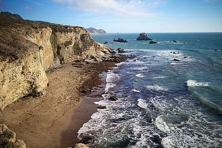 seashore near brown rocky mountain