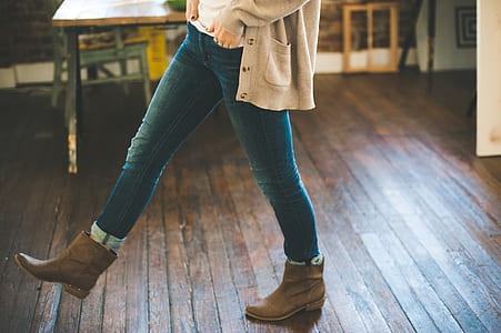 person wearing blue jeans and pair of brown leather booties