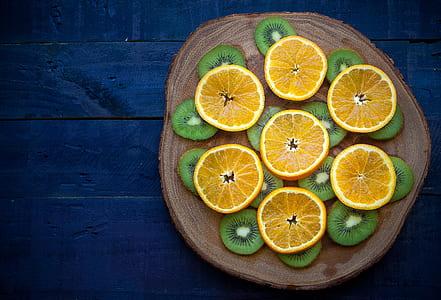 citrus fruit and kiwi on brown slab