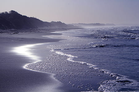 photo of sea wave near gray mountain
