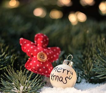 closeup photo of white Merry Xmass bauble