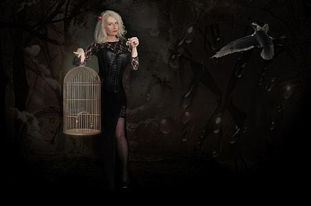 woman in black long-sleeved side-slit dress holding birdcage