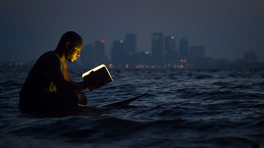 man holding a book on body of water