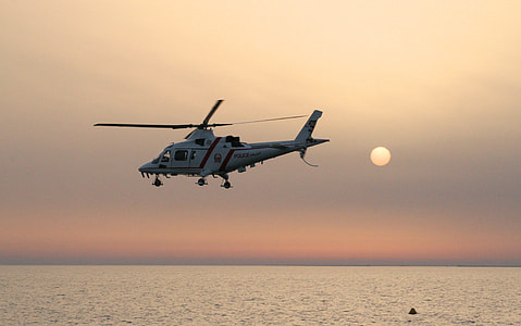 white helicopter hovering above body of water