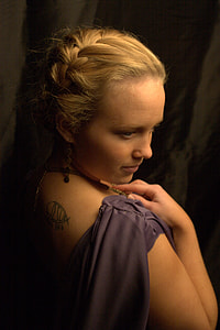 woman in purple sleeveless top with black back tattoo