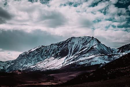 snow covered mountain under cloudy sky