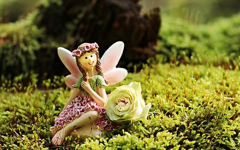 fairy figurine near white petal flower