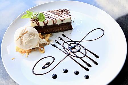 vanilla ice cream and white coated cake on top of round white ceramic plate