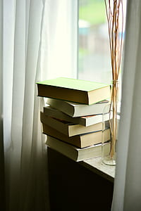 pile of books on window near glass vase