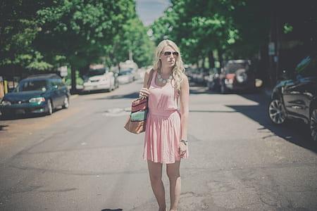 woman wearing pink scoop-neck sleeveless dress at street