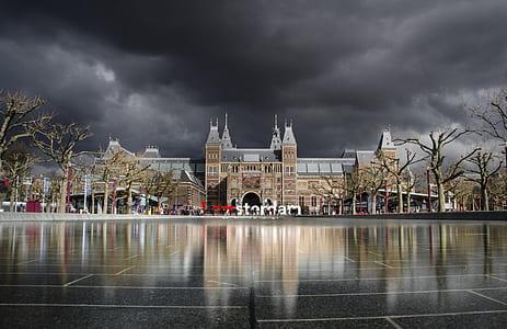 brown building under dark cloudy sky