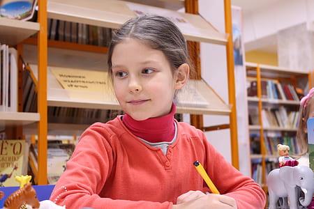 girl wearing red jacket holding yellow pen