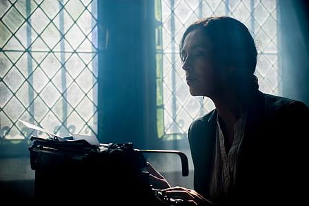woman in black top looking into black typewriter