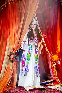 woman standing while holding orange and red curtain wearing multicolored angel sleeve long dress