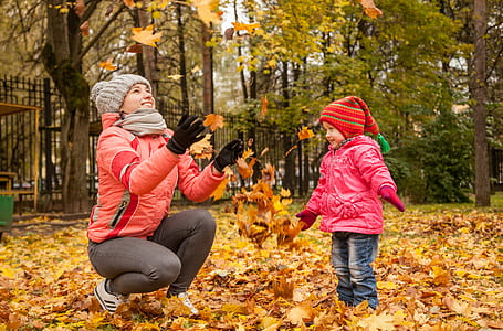 woman in red sweater tossing upward some brown leaves while a girl playing with it