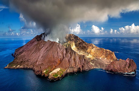 brown volcano on body of water