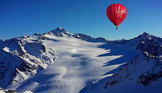 red Virgin air balloon near mountain