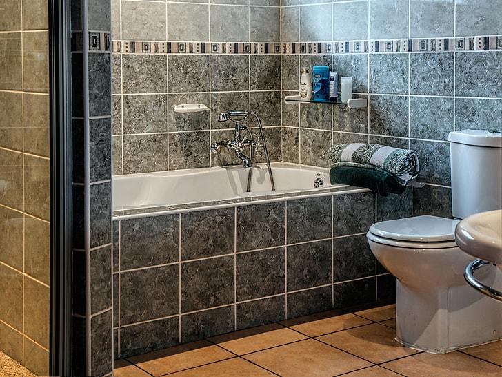 white ceramic toilet bowl with cistern and bathtub