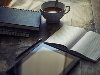 white ceramic mug beside open notebook
