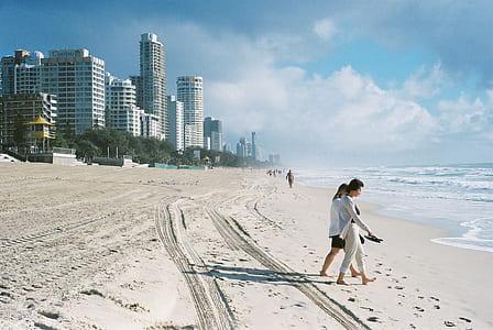 two women walking towards the beach