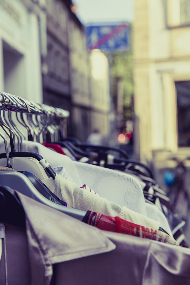 Shallow Focus Photography of Shirts Hang on Silver Clothes Rack Under Sunny Sky