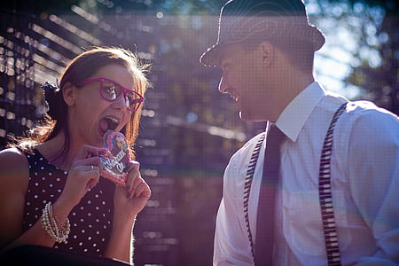 photograph of woman about to heat heart candy in front of a man in hat