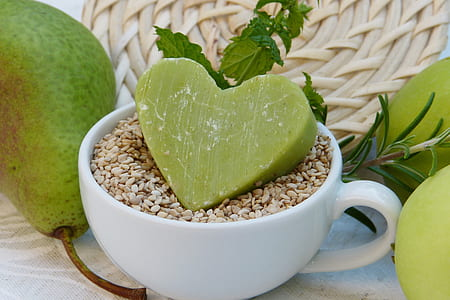 white ceramic cup beside green fruit