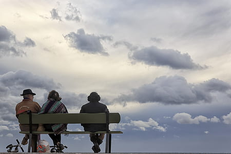 three person sitting on brown wooden bench during daytime photo