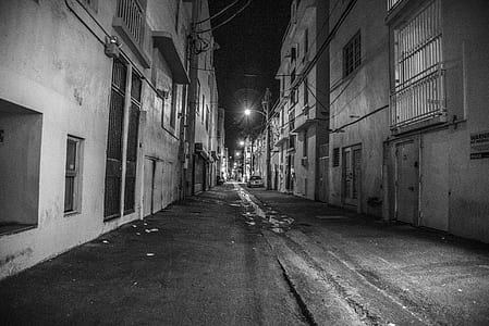 grayscale photography of street between buildings