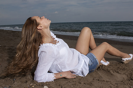 woman wearing white long-sleeved shirt and blue denim short shorts seats on brown sand