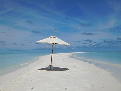 white and brown folding umbrella on beach