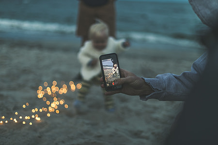 bokeh photography of person capturing baby