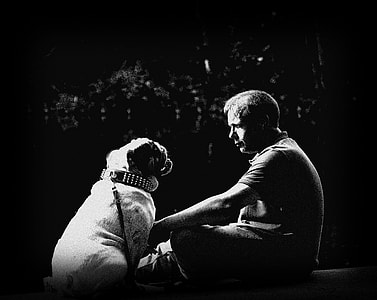 grayscaled photo of man holding dog