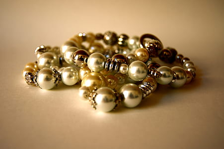 beaded gold-colored bracelets on beige surface