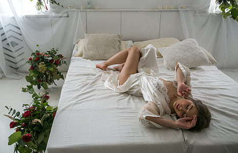 woman wearing white robe on top of white bed