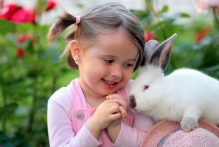 photo of girl in pink top beside white rabbit