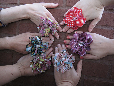 six hands laying on concrete brick with rosette rings