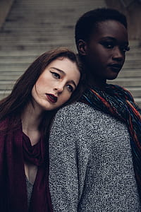 two women stands near white surface at daytime
