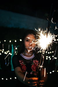 Woman Holding Sparkle during Nighttime