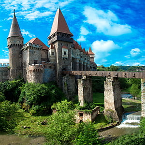 photo of brown stone castle with bridge