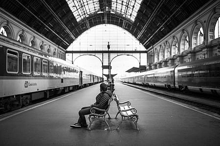 grayscale photo of man sitting on bench on train station