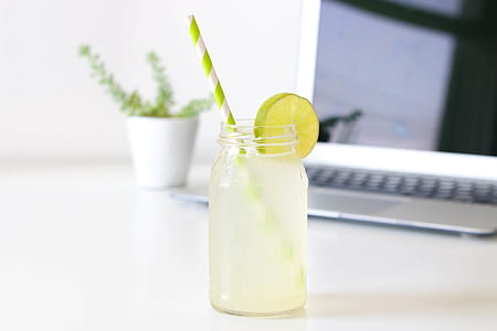 glass of citrus juice with disposable straw