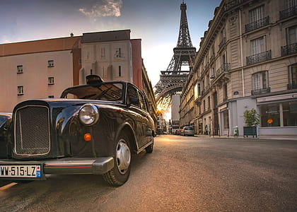 photo of black car on pavement with Eiffel Tower background
