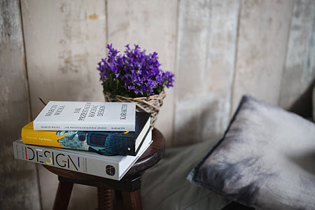Books and purple flowers on a wooden stool by the bed