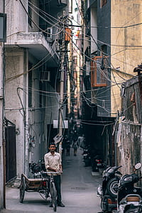 man leaning on trike under electricity cables
